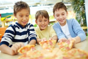 three boys eating pizza