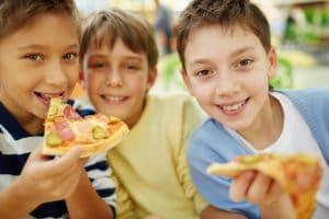Three boys eating pizza